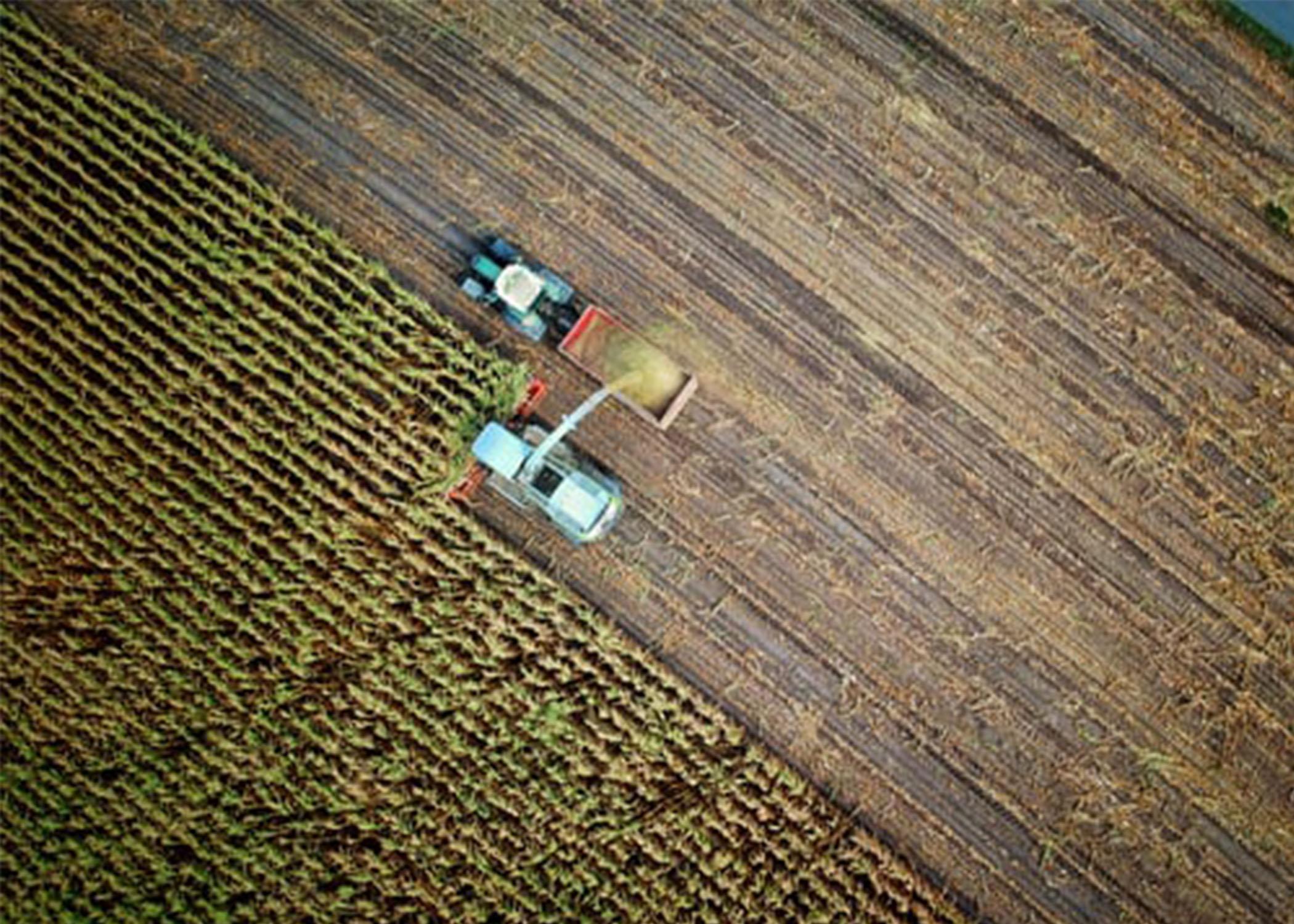 Ariel photo of two tractors on farmland.