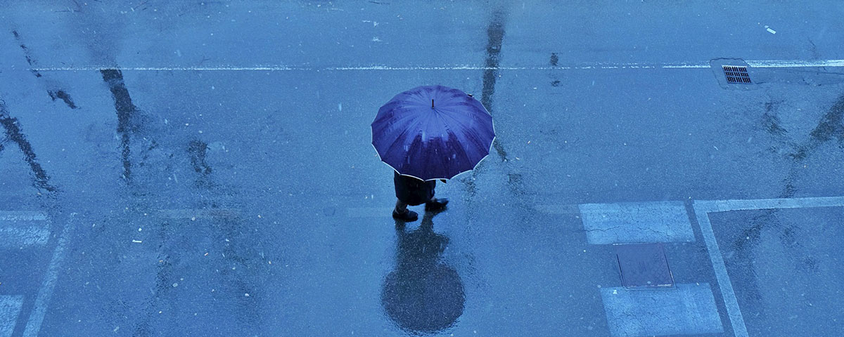 Image of person under umbrella on rainy street
