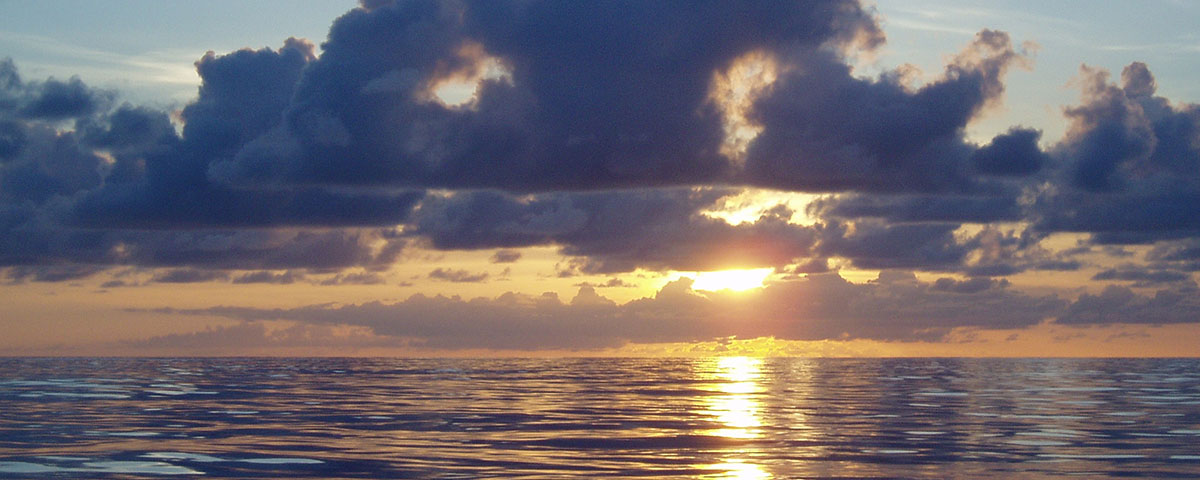 Photo of a tropical sunset over a placid sea in Hawaii