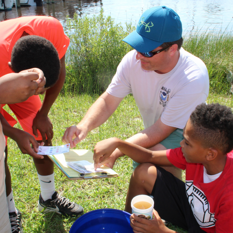 Photo of NCEI scientist helping STEM students test water