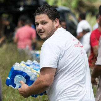 Local residents form a chain to deliver food and water to their community during humanitarian aid efforts in Puerto Rico following Hurricane Maria in 2017