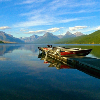 Photo of boats stored on a dock next to blue lake and mountain landscape