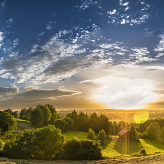 Photo of panoramic view of landscape with sun on horizon