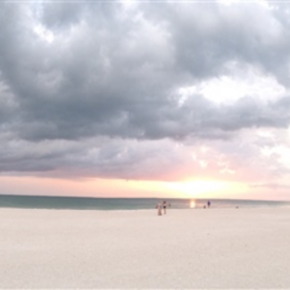 Photo of white beach at sunset with overcast sky