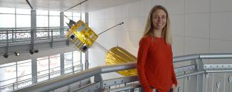 Meg Tilton standing in front of a model of the GOES-8 satellite