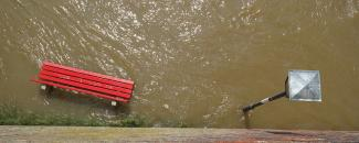 Park bench and street lamp during flood