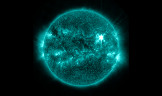 Image of a solar flare blazingly hot in the upper right of the sun