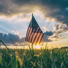 Photo of a field in the country with an American flag in it