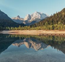 Photo of a lake with a dry shore in front of mountains