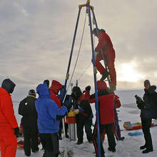 Photo of paleoclimatologists taking ice core samples in the Arctic