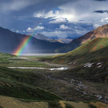 Photo of a rainbow over mountains in Alaska