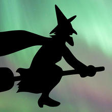 Artwork of a witch flying in front of an aurora