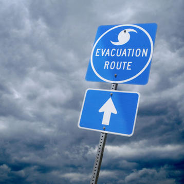 Photo of heavy clouds with a hurricane evacuation route sign