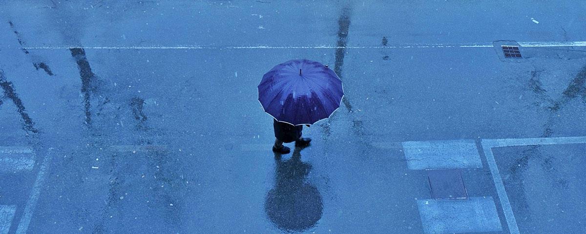 Image of person under umbrella on rainy street